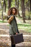 Curly hair teen girl with retro suitcase in autumn forest Royalty Free Stock Image