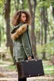 Curly hair teen girl with retro suitcase in autumn forest Stock Image
