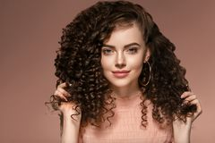 Curly hair woman hairstyle lady with long brunette hair. Studio shot stock image
