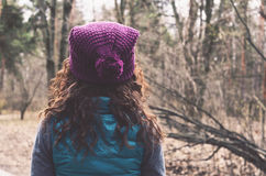 Curly hair woman in knitted hat in autumn forest Stock Images