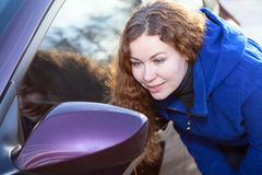 Curly hair woman looking in car back side mirror Royalty Free Stock Image