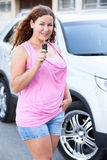 Curly hair woman in pink clothes showing car key in hand near own new car Stock Photography