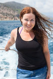 Curly hair young woman in sea cruise on yacht Stock Photos