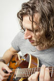 Curly hairdo. An image of a handsome man playing the guitar Stock Photo