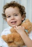 Curly-haired мальчик с плюшевым медвежонком стоковые изображения rf