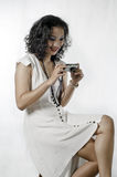 Curly-haired Asian woman operating a pocket camera. Royalty Free Stock Photo
