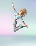 Curly-haired athlete woman jumping and dancing Royalty Free Stock Images