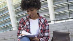 Curly-haired biracial girl sitting on stairs and writing something in notebook. Stock footage stock video
