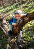 A blond girl in a forest. Белокурая девочка в лесу. A curly-haired blond small girl in a royalty free stock image