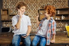 Curly haired brothers high fiving at home. Support is what really matters. Relaxed kids smiling while looking at each other and giving a high five during a Royalty Free Stock Photography