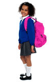 Curly haired elementary school girl. Carrying pink backpack on shoulders Royalty Free Stock Image
