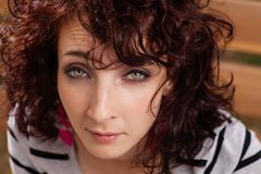 Curly haired female closeup portrait. Royalty Free Stock Images