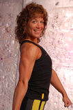 Curly haired fitness woman. Buff fitness woman with curly hair and gym attire smiling for the camera Royalty Free Stock Photography