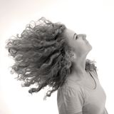 Curly-haired girl. Girl whipping her curly hair around Royalty Free Stock Image