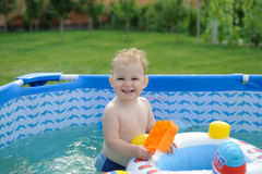 Curly haired girl in backyard pool Stock Photography