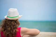 Curly haired girl at ocean coast. Rear view. Royalty Free Stock Photos