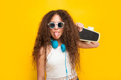 Curly haired girl showing tongue holding cruiser stock image