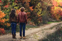Curly-haired guy and fair-haired girl in autumn standing unfolded with their backs on road. Curly-haired mustachioed guy and fair-haired girl in autumn standing royalty free stock images