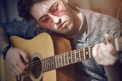 A curly-haired guy with pink glasses plays a wooden acoustic guitar melody royalty free stock images