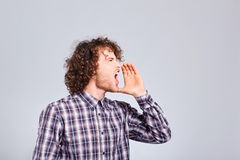 The curly-haired guy shouts raising his hand to his mouth with a stock photo