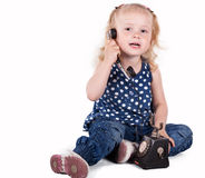 Curly-haired little girl with a vintage telephone. Isolated on white background stock photography