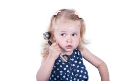Curly-haired little girl with a vintage telephone. Isolated on white background stock images