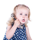 Curly-haired little girl with a vintage telephone. Isolated on white background royalty free stock image