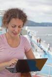 Curly-haired Mädchen mit Laptop auf Lieferung Lizenzfreies Stockfoto