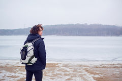 The curly haired man in a jacket with backpack winter at lake travels Stock Photo