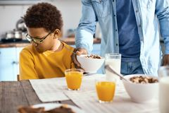 Curly-haired pre-teen boy not wanting to eat cereals Royalty Free Stock Image
