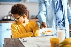 Curly-haired pre-teen boy refusing to eat fried egg royalty free stock photography