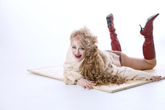 Curly-haired woman in a fur coat lying on the parquet Stock Images