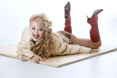 Curly-haired woman in a fur coat lying on the parquet Royalty Free Stock Image