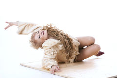 Curly-haired woman in a fur coat lying on the parquet Royalty Free Stock Images