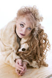 Curly-haired woman in a fur coat lying on the parquet. On white background Royalty Free Stock Image
