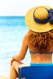 Curly haired woman looking at the sea Stock Photo