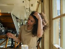 A curly-haired woman sits at a table in a cafe and straightens her hair royalty free stock images