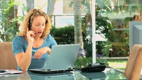 Curly haired woman speaking over the headset Stock Photo