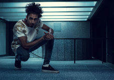 Curly-Haired Young Guy Squatting Inside a Building Royalty Free Stock Image