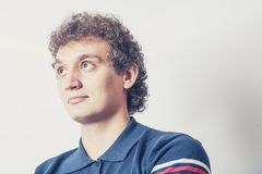 Curly haired young man on gray background with pensive expression. Stock Images