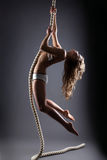 Curly-haired young woman hanging on rope Stock Photography