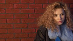 Curly haired young woman posing in front of brick wall.  stock video