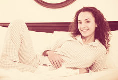 Curly haired young woman relaxing in bed Royalty Free Stock Image