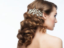 Curly Hairstyle. Portrait of attractive young woman with beautiful hairstyle with stylish hair accessory. Girl with long curly hair, rear view Stock Photo