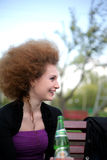 Curly happy girl drinking beer. On the nature of the day Royalty Free Stock Photography