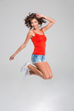 Curly happy young woman jumping and smiling. Curly happy carefree young woman in red top, jeans shorts and white sneackers jumping and smiling royalty free stock photography