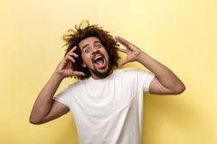 A curly-headed brunet man is shouting and holding his arms near the face. Bright emotions over the yellow background royalty free stock photos