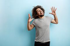 A curly-headed handsome man wearing a gray T-shirt is having fun with his tongue out, playful eyes and palms open and royalty free stock image