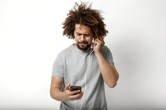 A curly-headed handsome man wearing a gray T-shirt is looking at the phone and listening to the earphones over the white stock image