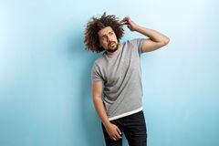 A curly-headed handsome man wearing a gray T-shirt and ripped jeans is standing and thinking with his hand raised and royalty free stock images